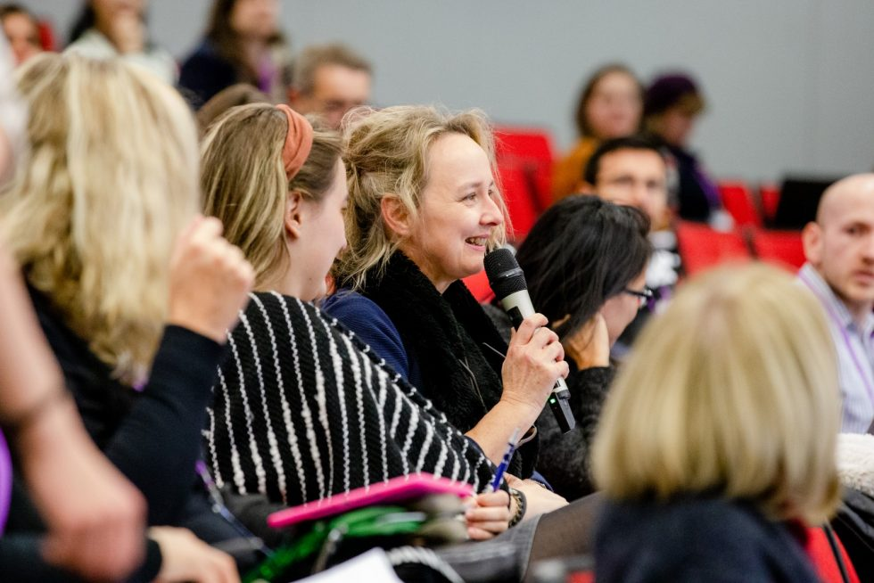 A photograph of a lady speaking into a microphone to a host at a NALDIC conference