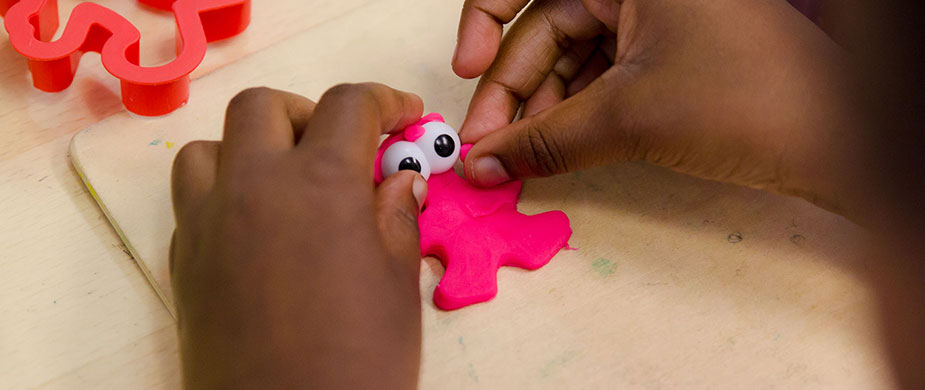 Close up photo of young girl's hands making plasticine creature