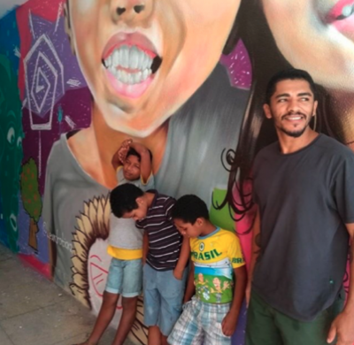A photo of a man with some children resting on a wall with graffiti on it